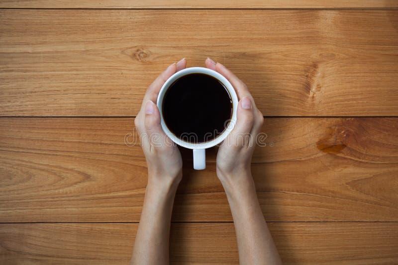 La donna passa a tazza della tenuta della bevanda calda quella condizione sulla linguetta di legno fotografia stock libera da diritti