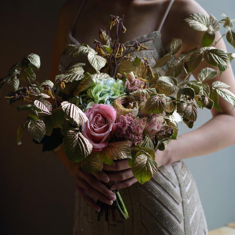 La donna passa la tenuta del mazzo decorato bello dei fiori, tiro del primo piano fotografia stock