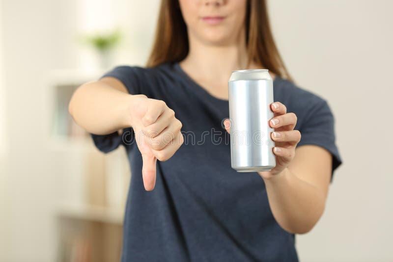 La donna passa la tenuta della bevanda della soda può con i pollici scolarsi fotografia stock