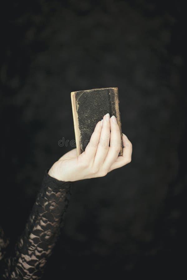 La donna passa a tenuta il vecchio libro d'annata, colpo rurale e gotico sensuale atmosferico molto scuro dello studio immagini stock libere da diritti