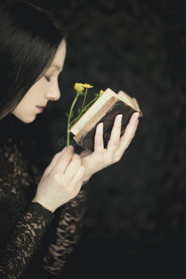 La donna passa a tenuta il vecchio libro d'annata, colpo rurale e gotico sensuale atmosferico molto scuro dello studio fotografia stock libera da diritti