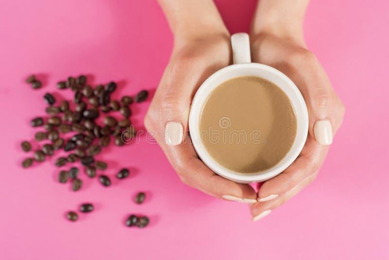 La donna passa la tenuta la tazza di caffè e dei chicchi di caffè vaghi sullo scrittorio rosa immagine stock libera da diritti