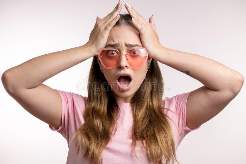 La donna pazza colpita in occhiali da sole alla moda sta tenendo la sua testa fotografia stock