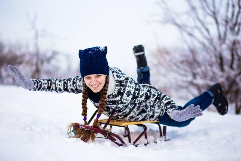 La donna pazza gode del giro della slitta Sledding della donna Gioco divertente della donna all'aperto in neve Divertimento all'a fotografie stock libere da diritti