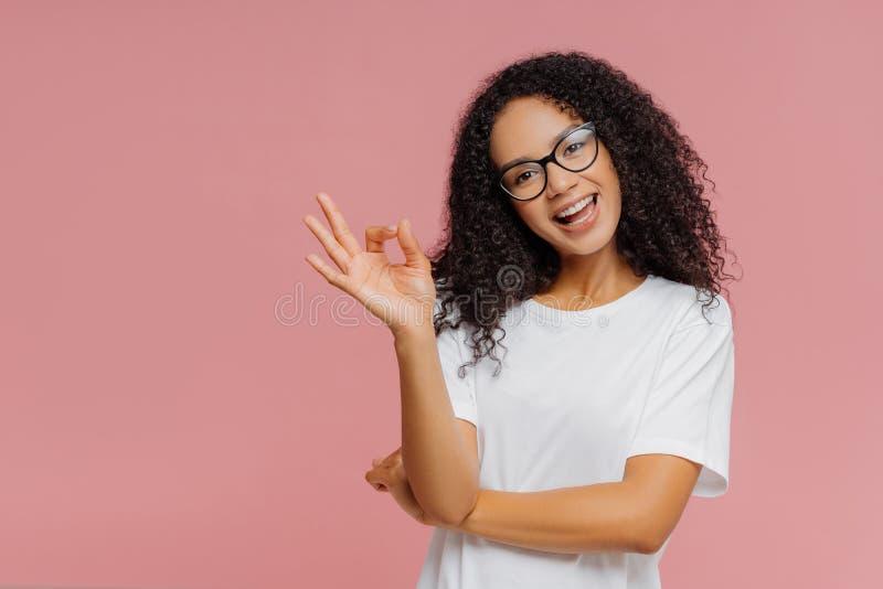 La donna pelata scura adorabile ottimista fa il gesto giusto, inclina la testa, dimostra l'approvazione, è d'accordo con qualcosa fotografie stock libere da diritti