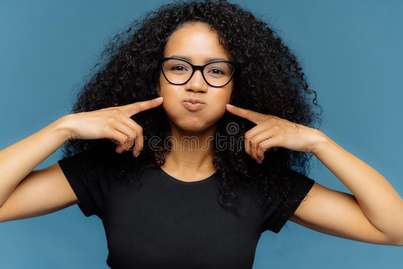 La donna pelata scura divertente con capelli ricci, preme le guance, trattiene il respiro, soffia le guance, porta i vetri ottici fotografia stock