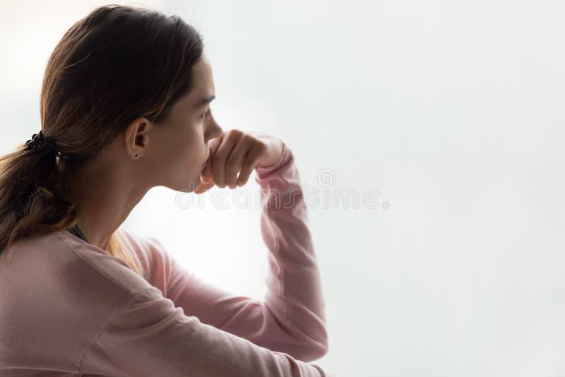 La donna pensierosa che si siede all'interno ha perso sul fronte di vista laterale di pensieri fotografie stock libere da diritti