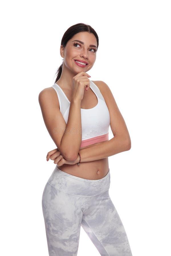 La donna pensierosa di forma fisica rispetta il lato mentre sorride fotografia stock
