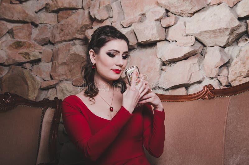 La Donna In Un Vestito Rosso Guarda Nello Specchio ...