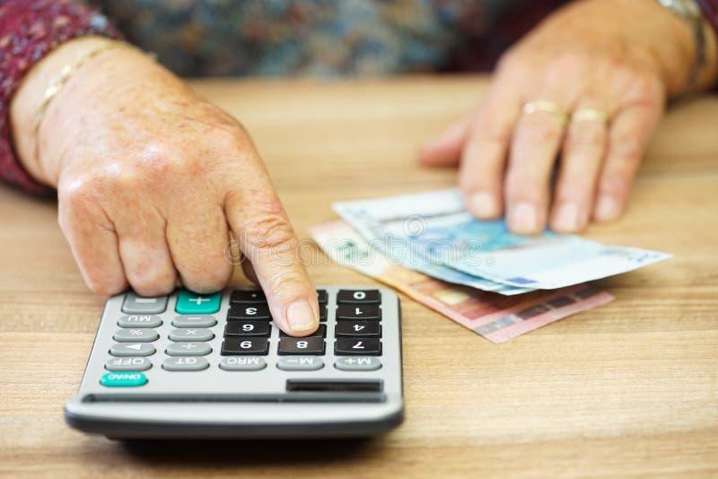 La donna più anziana sta utilizzando il calcolatore per calcolare tutte le spese fotografia stock libera da diritti