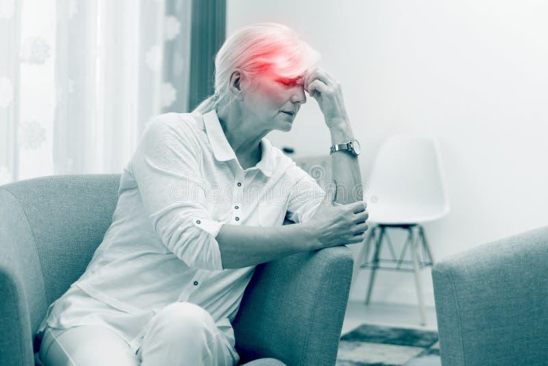 La donna pi? anziana ha un'emicrania fotografia stock