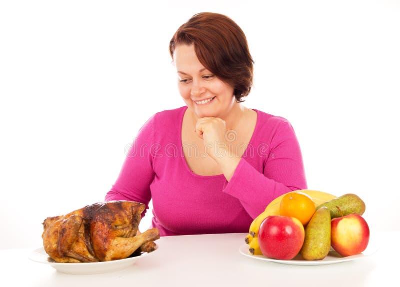 La donna piena sceglie che cosa mangiare immagini stock libere da diritti