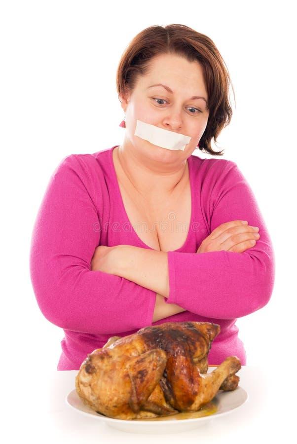La donna piena su una dieta, vuole mangiare il pollo immagini stock