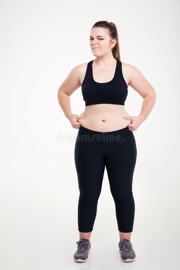 La donna pizzica il grasso sulla sua pancia fotografia stock