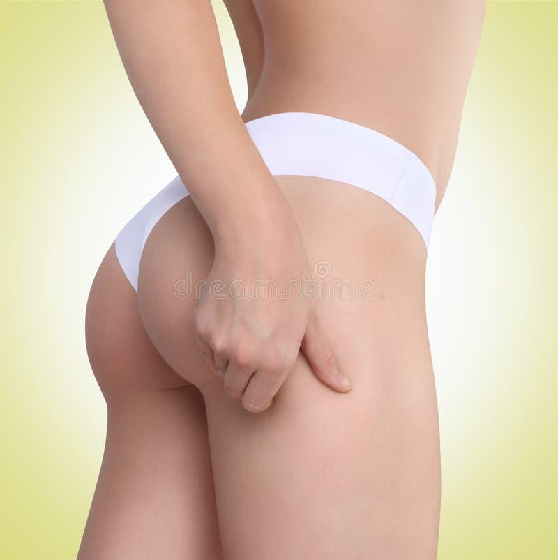 La donna pizzica la sua coscia per controllare le celluliti immagine stock