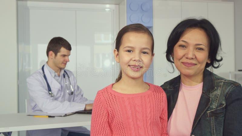 La donna posa con sua figlia all'ospedale del ` s dei bambini immagine stock libera da diritti