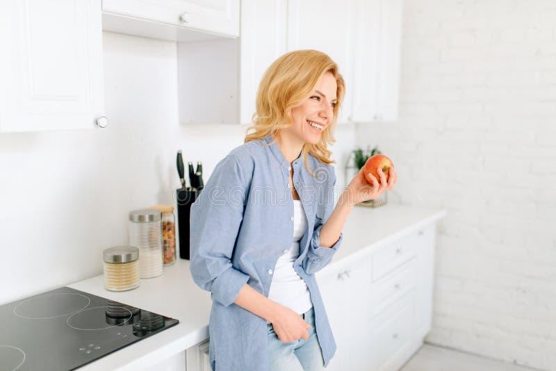 La donna posa sulla cucina con l'interno bianco come la neve immagine stock libera da diritti