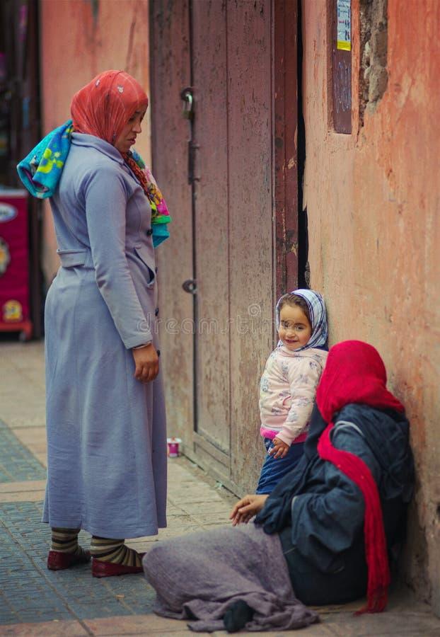 La donna povera ed il bambino del mendicante si siedono in via della città con il vestito tradizionale dalla mussola, Marrakesh,  fotografia stock libera da diritti