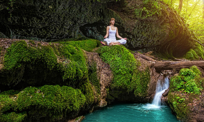 La donna pratica l'yoga in natura, la cascata posa di sukhasana immagine stock libera da diritti