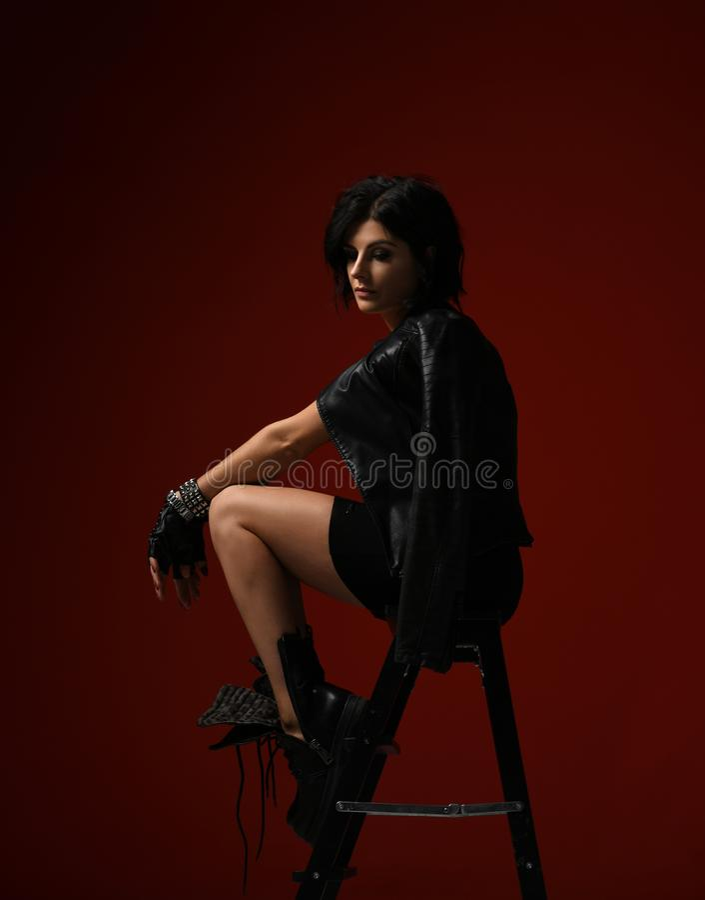 La donna premurosa in vestito stretto nero, in bomber ed in grandi stivali brutali sedentesi su una scala a libro e guarda dall'a fotografia stock libera da diritti