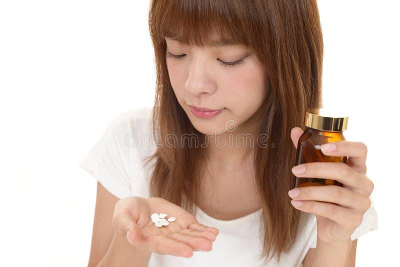 La donna prende i supplementi immagine stock