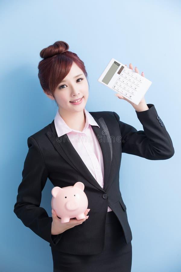 La donna prende il porcellino salvadanaio rosa fotografia stock