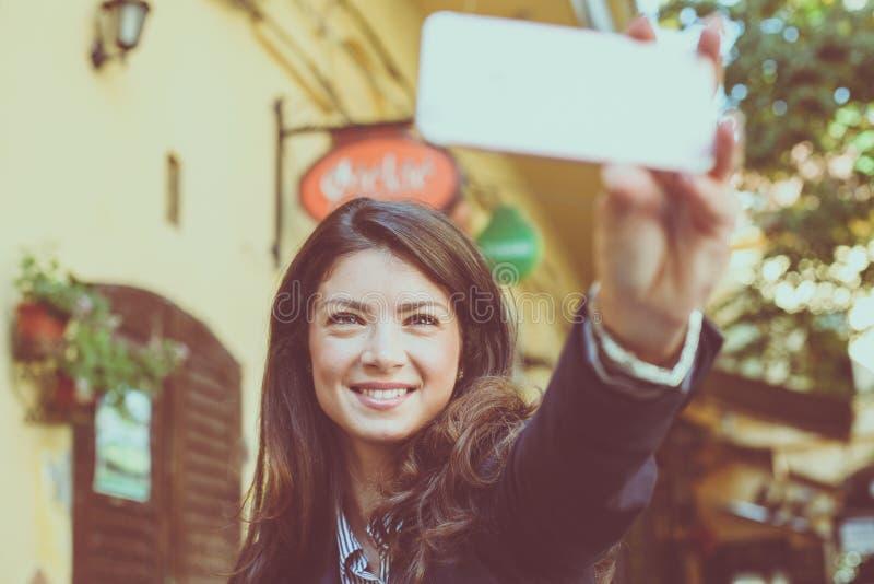 La donna prende un autoritratto Fuoco sul telefono fotografie stock libere da diritti