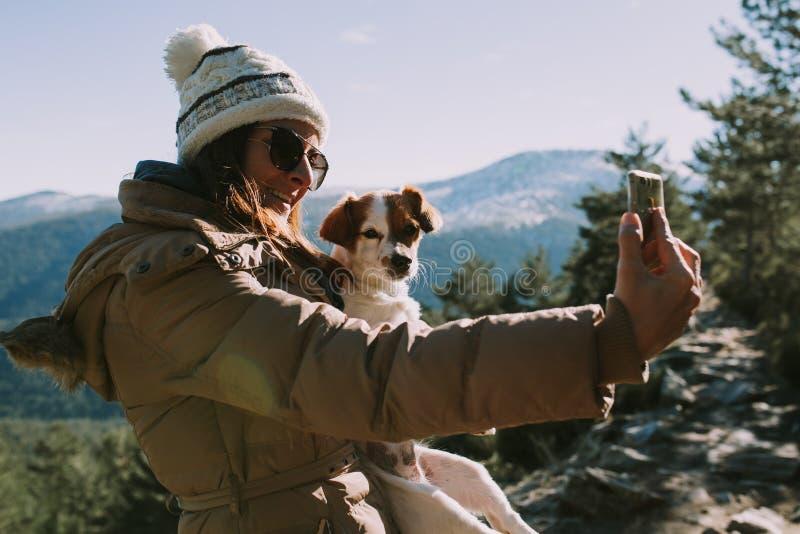 La donna prende un'immagine con il suo cane sulla montagna immagini stock libere da diritti