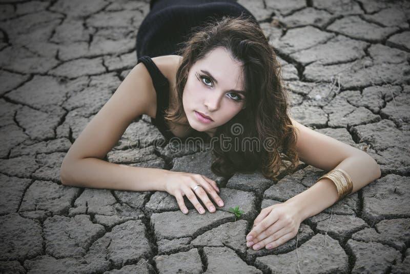 La donna protegge un piccolo germoglio su un suolo desertico incrinato immagini stock libere da diritti