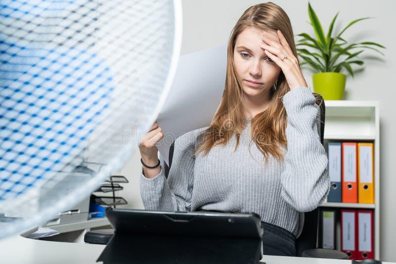 La donna può più non stare il calore nell'ufficio immagini stock libere da diritti