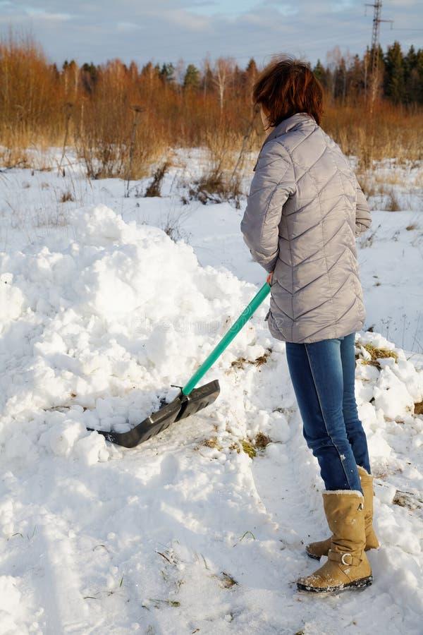 La donna pulisce la neve immagine stock libera da diritti