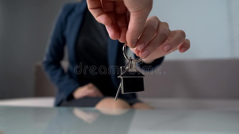 La donna ricca che prende le chiavi forma l'agente immobiliare, l'appartamento nuovo d'acquisto o l'ufficio fotografia stock libera da diritti