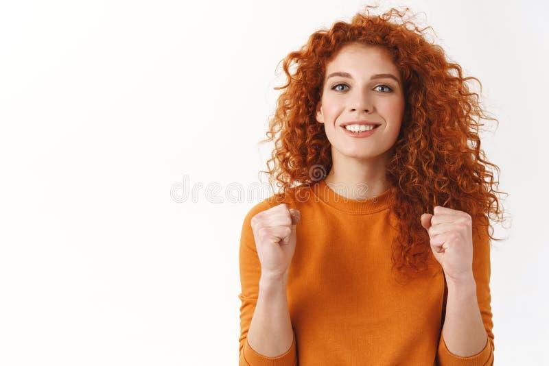 La donna riccio-dai capelli splendida felice che incoraggia, pompa della testarossa del pugno, serra le armi e sorridere eccitato immagine stock