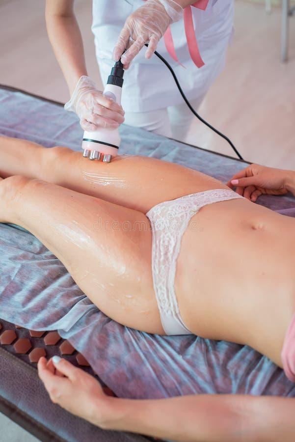 La donna riceve un massaggio elettrico contro la cellulite Il medico esegue la correzione della cavitazione ultrasonica del corpo fotografie stock libere da diritti