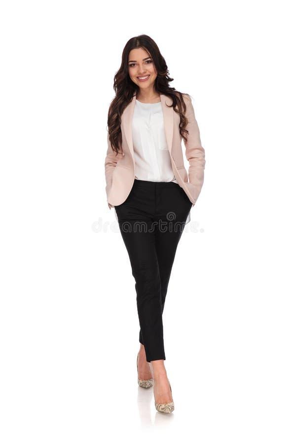 La donna rilassata felice di affari con le mani in tasche sta camminando fotografia stock libera da diritti