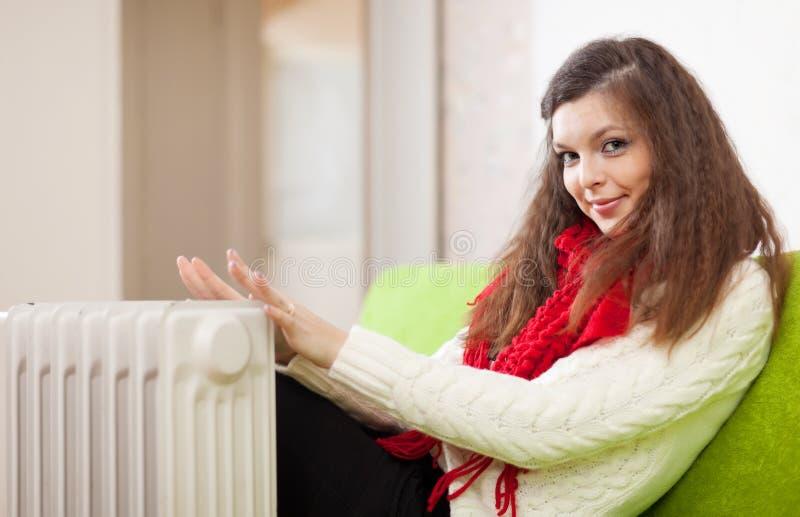 La donna riscalda le mani vicino a calorifer a casa fotografia stock libera da diritti