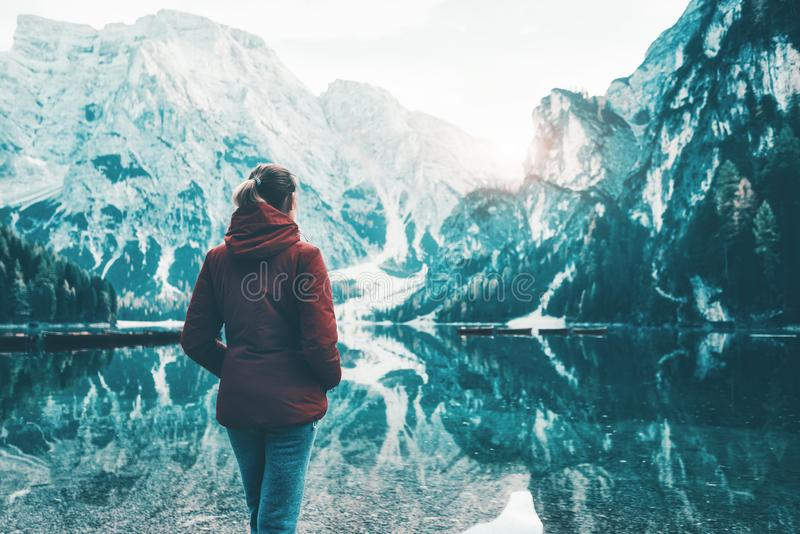 La donna in rivestimento rosso sta stando sulla costa del lago Braies fotografia stock