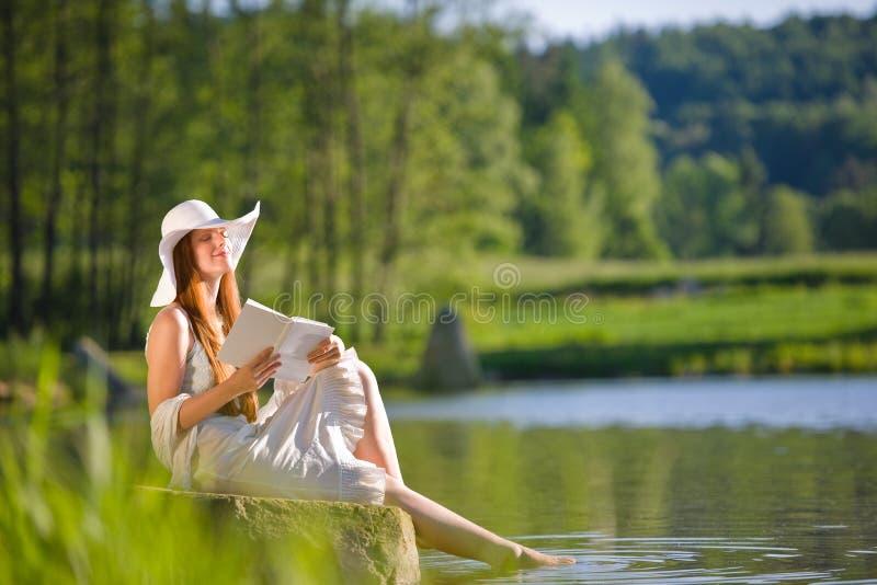 La donna romantica dei capelli rossi si distende dal lago con il libro immagine stock libera da diritti