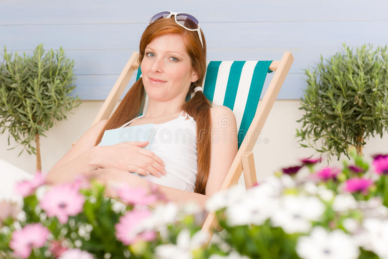 La donna rossa dei capelli del terrazzo di estate si distende nel deckchair immagine stock libera da diritti