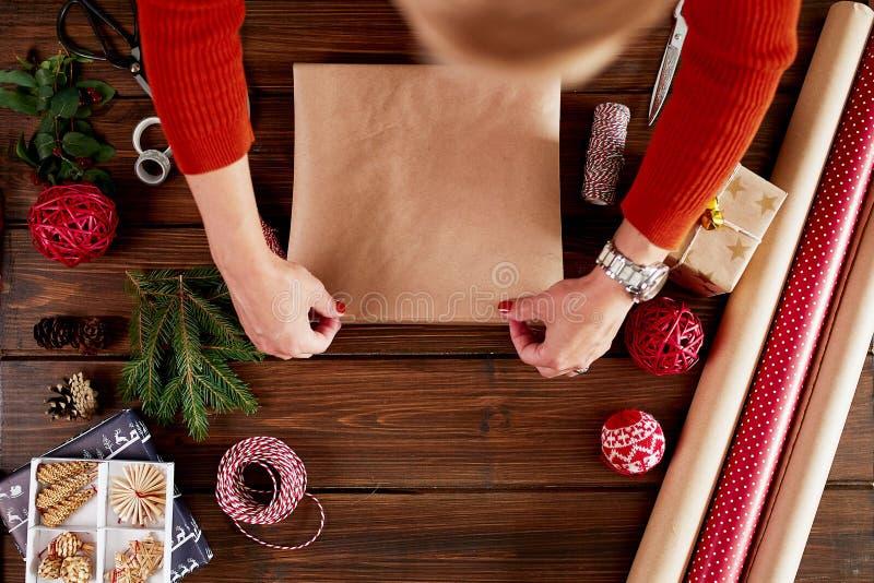 La donna s passa lo spostamento del regalo di Natale su fondo di legno scuro immagine stock libera da diritti