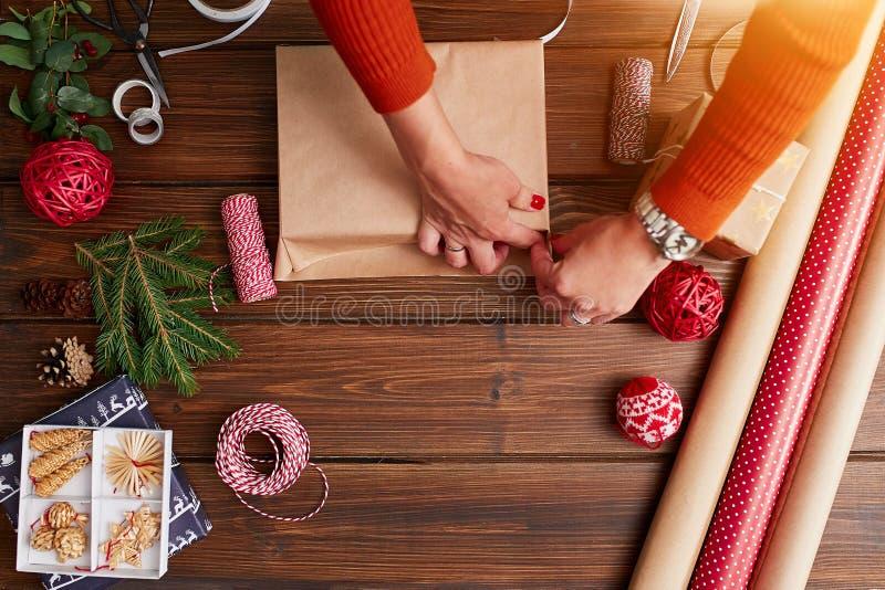La donna s passa lo spostamento del regalo di Natale su fondo di legno scuro fotografia stock libera da diritti