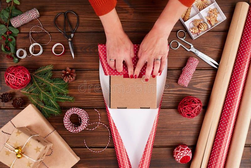 La donna s passa lo spostamento del regalo di Natale su fondo di legno scuro fotografia stock