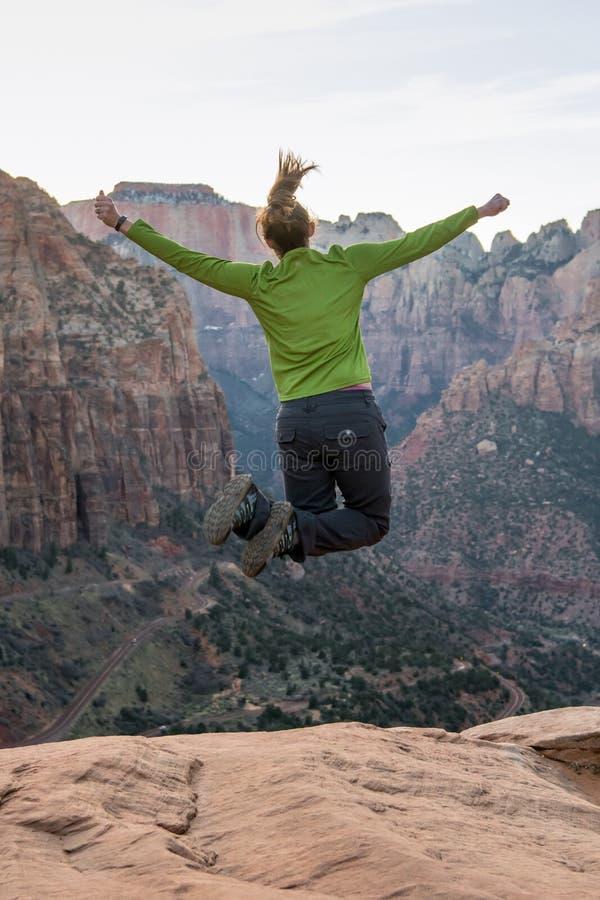 La donna salta su davanti al vasto canyon fotografia stock libera da diritti
