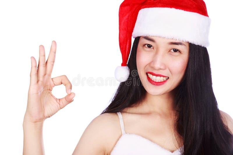 La donna in Santa Claus rossa copre la mostra del segno giusto isolato sul whi fotografie stock libere da diritti