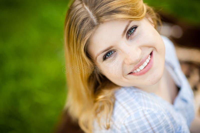 La donna sbalorditiva esamina indietro la macchina fotografica con un sorriso immagine stock libera da diritti