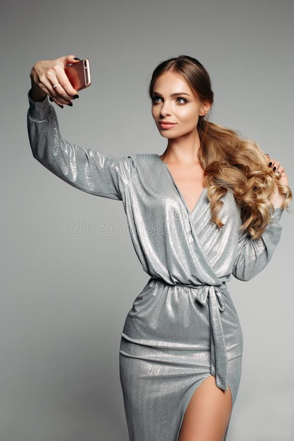 La donna sbalorditiva nella notte d'argento fuori si veste con capelli ondulati lunghi Tak immagini stock