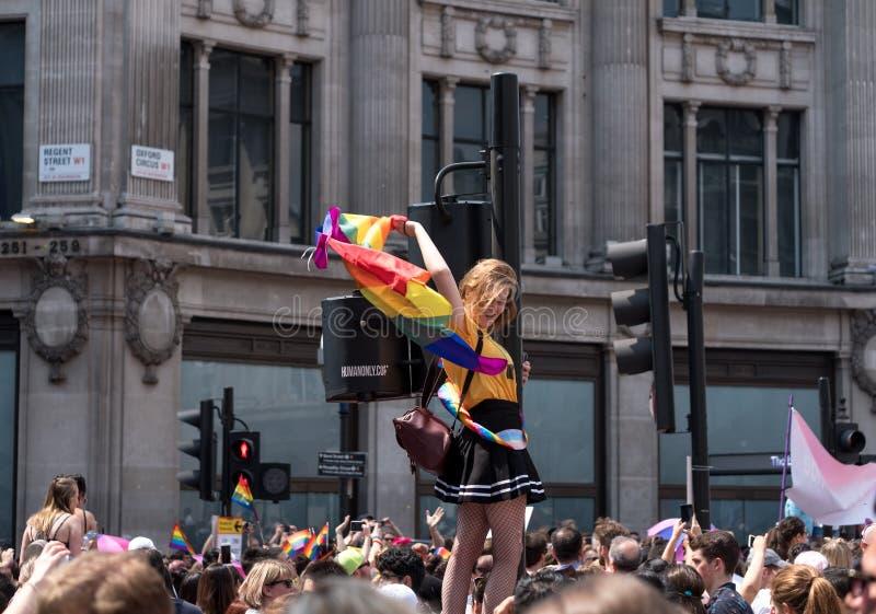 La donna scala il semaforo al circo di Oxford, Londra, per ottenere un migliore punto di vista di Pride Parade gay fotografie stock