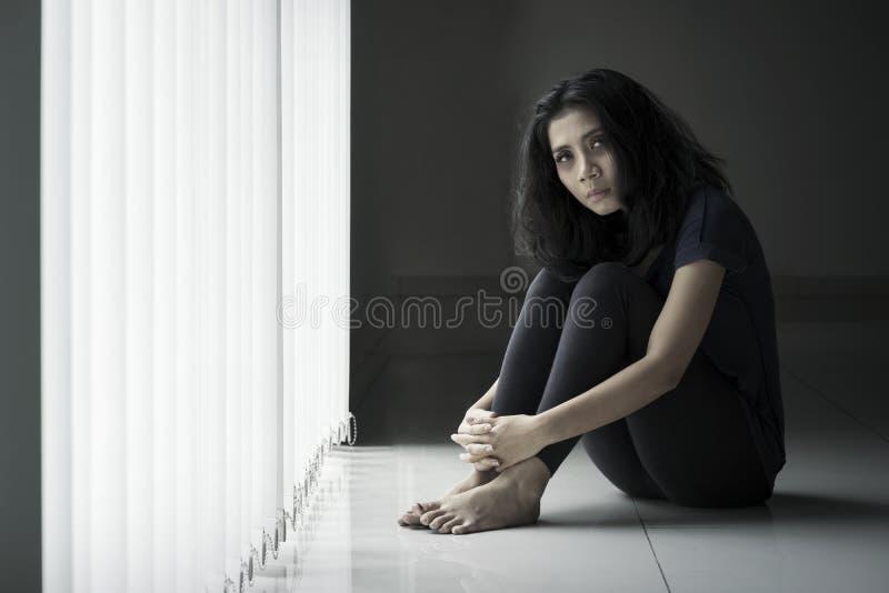 La donna scarna sollecitata si siede vicino alla finestra fotografia stock libera da diritti