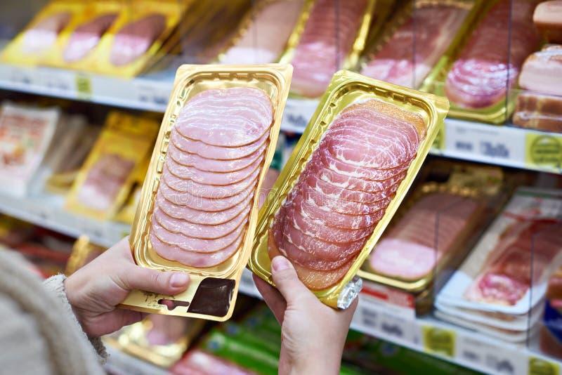 La donna sceglie la fetta di prosciutto al deposito fotografia stock