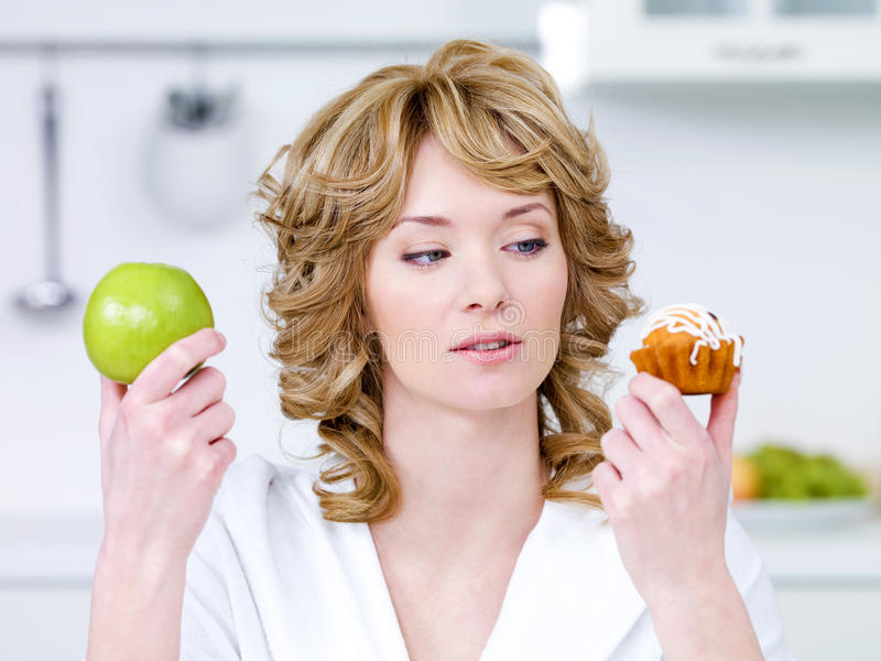 La donna sceglie fra la torta e la mela fotografia stock